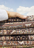 Persian carpet. A pile of Iranian handmade  carpets and rugs in a nice design in a nice blue sky background with a hand on it Royalty Free Stock Images