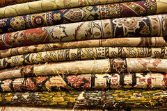 Carpet. A pile of Iranian and persian carpets on the shelf of shop for sale Stock Image