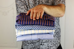 Pile of ironing shirts and hand Royalty Free Stock Image