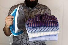 Pile of ironing shirts and hand Stock Photo
