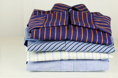 Pile of ironing shirts and hand Royalty Free Stock Photography