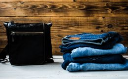 Pile of jeans and bag on a wooden background. A pile of jeans and bag on a wooden background Royalty Free Stock Photography