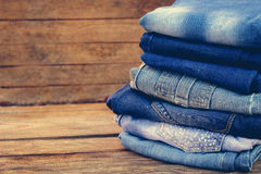 Pile of jeans clothes. On wooden background. Toned image Stock Photos