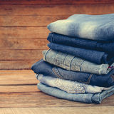 Pile of jeans clothes. On wooden background. Toned image Stock Images