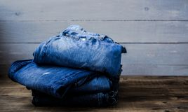 A pile of jeans. On a grey wooden background Royalty Free Stock Image