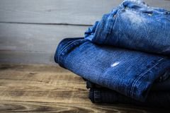 A pile of jeans. On a grey wooden background Stock Images