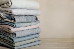 Pile of jeans and knitted clothes sweaters, scarves, pullovers. Blue, white and grey colors. Selective focus Royalty Free Stock Photography