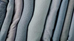 Pile of jeans and knitted clothes sweaters, scarves, pullovers. Blue, white and grey colors. Selective focus Stock Images
