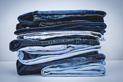 Pile of Jeans. Over grey Royalty Free Stock Image
