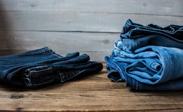 A pile of jeans. On a grey wooden background Stock Photo