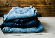 A pile of jeans. On a wooden background Royalty Free Stock Photos
