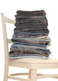 A pile of jeans. Is on white chair Royalty Free Stock Images