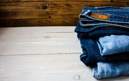 A pile of jeans. On a wooden background Royalty Free Stock Photography