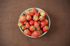 Pile of juicy ripe organic fresh strawberries in a large blue bowl. Dark background. Empty space Royalty Free Stock Photo