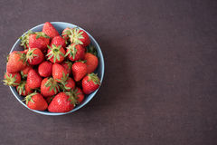 Pile of juicy ripe organic fresh strawberries in a large blue bowl. Dark background. Empty space Royalty Free Stock Images