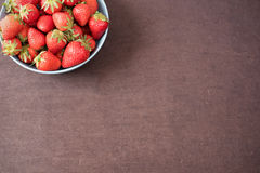 Pile of juicy ripe organic fresh strawberries in a large blue bowl. Dark background. Empty space Royalty Free Stock Photos