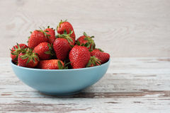 Pile of juicy ripe organic fresh strawberries in a large blue bowl. Light rustic wooden background Royalty Free Stock Photography