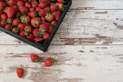 Pile of juicy ripe organic strawberries in a wooden box, crate, on a white background Royalty Free Stock Photography