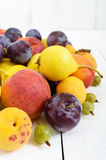 A pile of juicy summer fruits on white wooden background plums, apricots, pears. Stock Photo