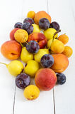 A pile of juicy summer fruits on white wooden background plums, apricots, pears. Stock Photos