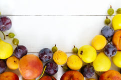A pile of juicy summer fruits on white wooden table plums, apricots, pears. Royalty Free Stock Image