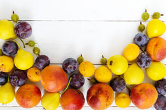 A pile of juicy summer fruits on white wooden table plums, apricots, pears Royalty Free Stock Image
