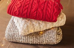 A pile of warm sweaters on the tissue background decorated with lights stock image