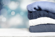 Pile knitted winter autumn clothes on wooden background. royalty free stock images