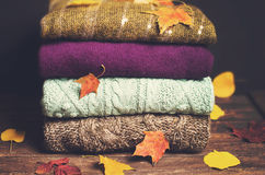 Pile of knitted winter clothes on wooden background covered with