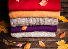 Pile of knitted winter clothes on wooden background covered with Royalty Free Stock Photography