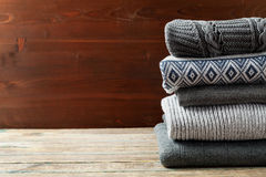 Pile of knitted winter clothes on wooden background, sweaters, knitwear Stock Image