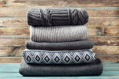 Pile of knitted winter clothes on wooden background, sweaters, knitwear. Space for text Stock Photography