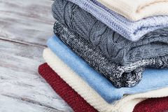 Pile of knitted winter clothes and wool sweaters on wooden background. Pile of knitted winter clothes and wool sweaters on rustic wooden background Royalty Free Stock Images