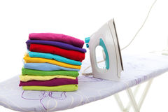 Pile of laundry and iron on ironing board Royalty Free Stock Photos