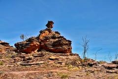Pile of layered rocks on rugged landscape under blue sky in Australia