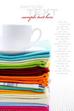 Pile of linen kitchen towels. And cup of tea or coffee over white (with sample text Royalty Free Stock Photography