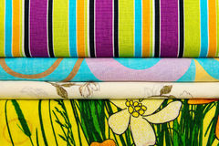 Pile of linen. A pile of multi-colored bed linen and towels. Bright mottled background Royalty Free Stock Images