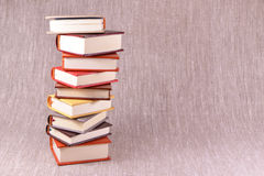 A pile of little books on a linen background Stock Images