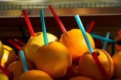 Pile of local fresh delicious high vitamin squeeze whole orange fruit juice with big colorful straws selling on street side Stock Photos