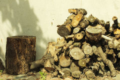 Pile of logs next to a cut tree. Pile of logs in front of an old house in Europe Royalty Free Stock Photography
