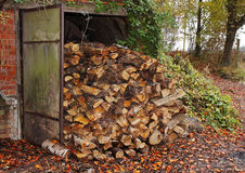 Pile of Logs by an old Hut Royalty Free Stock Photography