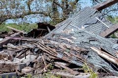 Pile of lumber used to be a strong old barn. Old pile of lumber and shingles used to be a strong old barn in Michigan USA until spring storms destroyed the Royalty Free Stock Image