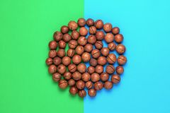 Pile macadamia nuts on blue green background. Pile macadamia nuts in the shape circle on blue green background. Duotone effect royalty free stock images