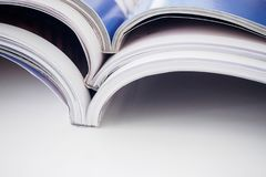 Pile of magazines stack on white table in living room. Close up Royalty Free Stock Photography