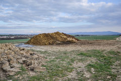 Pile of manure in the countryside with blue sky. Heap of dung in field on the farm yard with village in background. Traditional rural scene. Slovak landscape Stock Photo