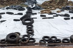 Pile of manure covered with a white tarpaulin. Pressed by old tires Royalty Free Stock Photos