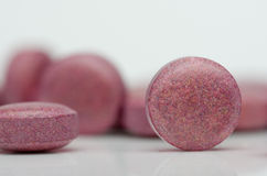 Pile of many small red pills, group of vitamins. Red pills on a Royalty Free Stock Photography