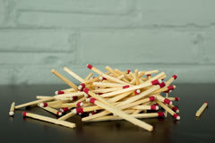 Pile of matches against brick wall background Royalty Free Stock Image