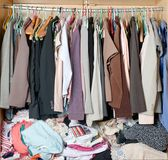Pile of messy clothes in closet. Untidy cluttered woman wardrobe stock images