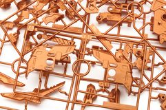 A pile of metallic orange plastic scale model kit set with futuristic robotic parts. A photo taken on a pile of metallic orange colored plastic scale model kit royalty free stock images